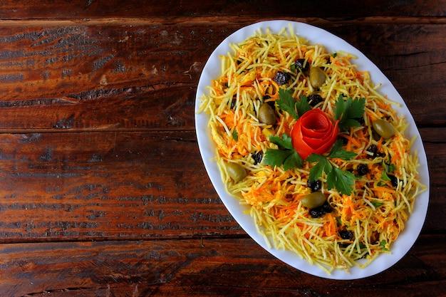 Il salpicao è un'insalata tipica brasiliana, a base di pollo tagliuzzato, uva passa, carota grattugiata, bastoncini di patate e maionese. Foto Premium