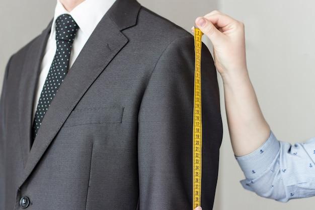 Il sarto prende le misure dal vestito, fondo bianco, isolato Foto Premium