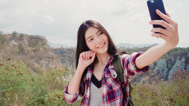 Il selfie asiatico della donna con zaino e sacco a pelo sopra la montagna, giovane femmina felice facendo uso del telefono cellulare che prende il selfie gode delle feste sull'escursione dell'avventura. Foto Gratuite