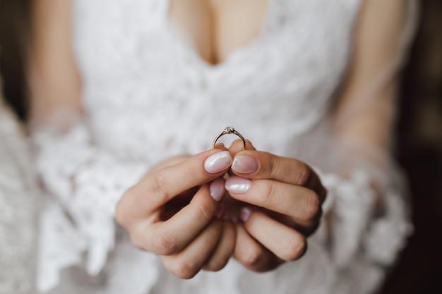 Il seno della giovane sposa si è vestito in vestito da sposa con l'anello di fidanzamento in mani con il diamante Foto Gratuite