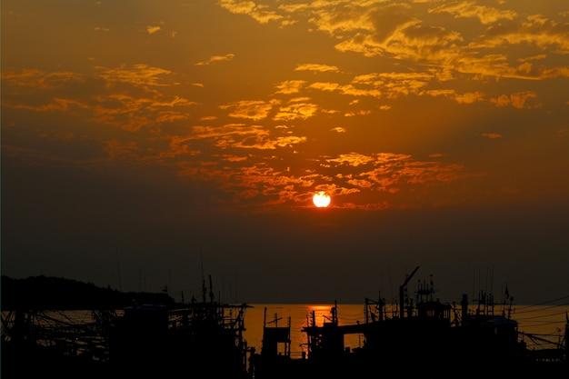 Il sole prima del tramonto sulla barca del pescatore alla tailandia Foto Premium