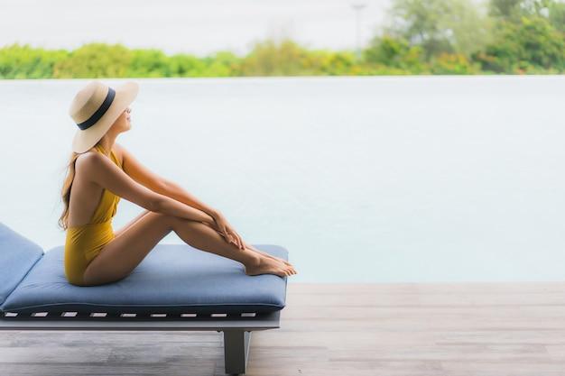 Il sorriso felice della bella giovane donna asiatica del ritratto si rilassa intorno alla piscina all'aperto nella vacanza di festa Foto Gratuite