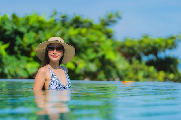 Il sorriso felice della bella giovane donna asiatica del ritratto si rilassa nella piscina alla spiaggia vicina dell'oceano del mare della località di soggiorno dell'hotel sul cielo blu Foto Gratuite