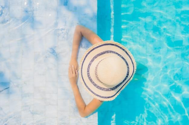 Il sorriso felice della bella giovane donna asiatica del ritratto si rilassa nella piscina per la vacanza di viaggio Foto Gratuite
