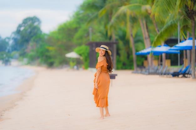 Il sorriso felice della bella giovane donna asiatica del ritratto si rilassa sull'oceano del mare della spiaggia Foto Gratuite