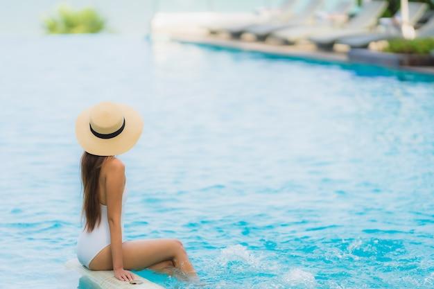 Il sorriso felice della giovane donna asiatica del ritratto si rilassa intorno alla piscina nella località di soggiorno dell'hotel Foto Gratuite