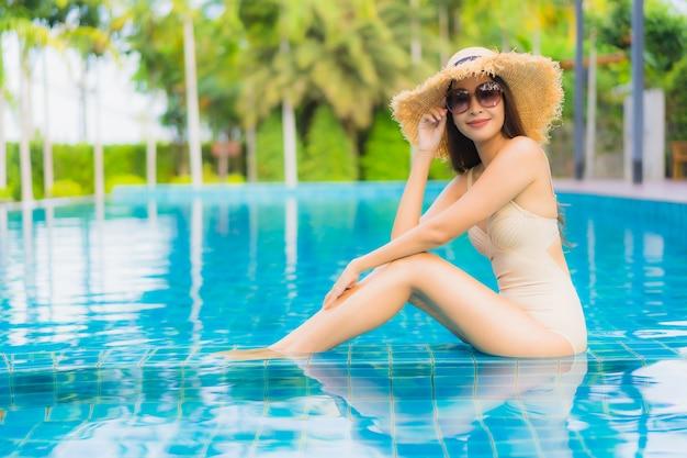Il sorriso felice delle belle giovani donne asiatiche del ritratto si rilassa la piscina all'aperto nella località di soggiorno Foto Gratuite