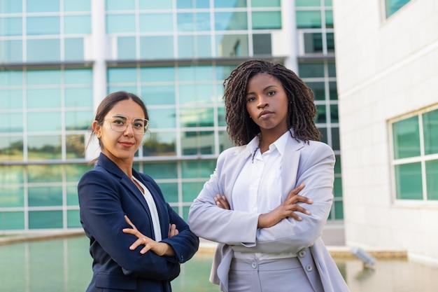 Il successo della miscela ha corso le donne di affari che posano con le mani incrociate Foto Gratuite
