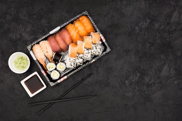 Il sushi del sashimi ha messo con soia e wasabi su fondo nero Foto Gratuite