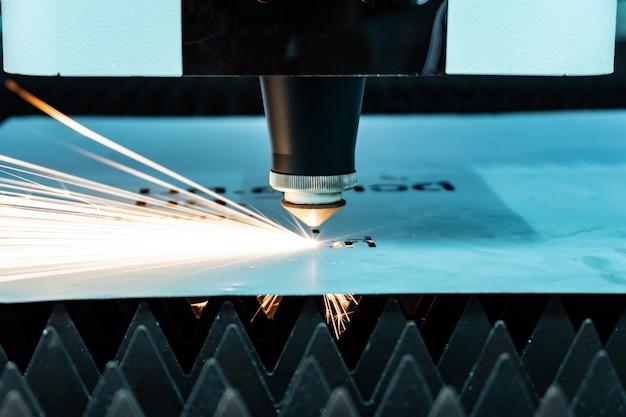 Il taglio di scintille metalliche vola dal laser Foto Premium