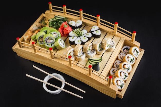 Il tavolo di sushi con la california, l'avocado, il hosomaki e la tempura rotola su una tavola di legno Foto Premium