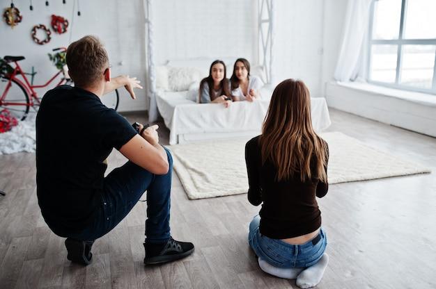 Il team di due fotografi che fotografano due gemelle modella le ragazze in studio. fotografo professionista al lavoro. Foto Premium