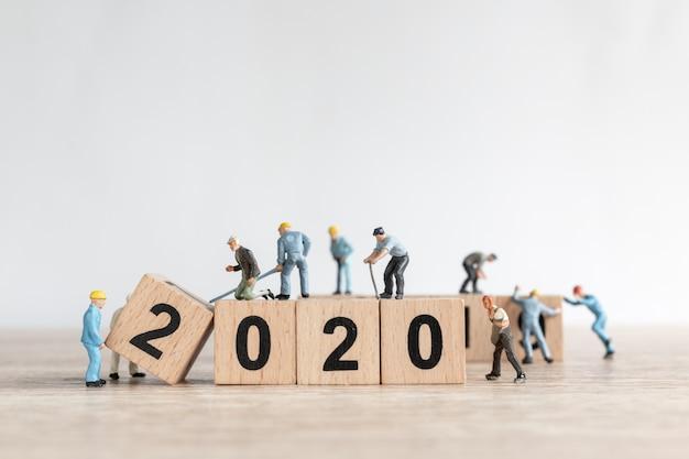 Il team di lavoratori in miniatura crea il numero 2020 Foto Premium