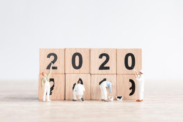 Il team di lavoratori in miniatura ha dipinto il numero 2020 e rimuove il numero 2019 Foto Premium