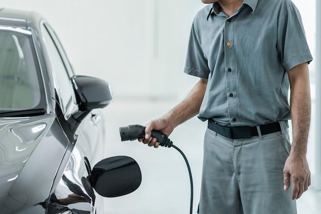 Il tecnico asiatico senior sta caricando l'auto elettrica o il veicolo elettrico nel centro servizi per manutenzione Foto Premium