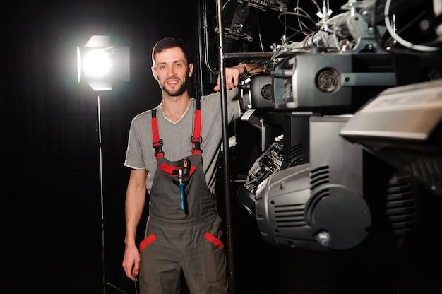 Il tecnico dell'illuminazione ripara il dispositivo luminoso sul palco. Foto Premium