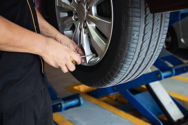 Il tecnico è gonfiare la gomma dell'auto, il servizio di manutenzione dell'auto sicurezza del trasporto Foto Gratuite