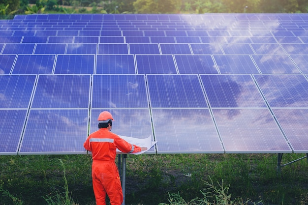 Il tecnico elettrico e strumentale usa un piano per pianificare e mantenere l'impianto elettrico nel campo dei pannelli solari Foto Premium
