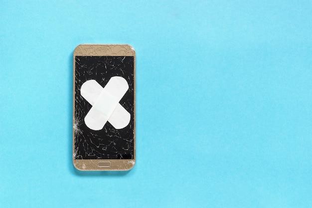 Il telefono rotto con lo schermo incrinato è coperto da cerotto medico di cerotto Foto Premium