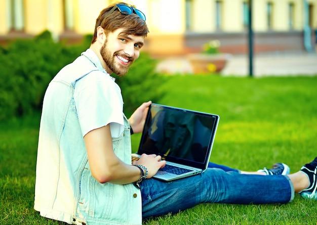 Il tipo bello sorridente dell'uomo divertente dei pantaloni a vita bassa in vestiti alla moda dell'estate nella via che posa la seduta sull'erba con il taccuino Foto Gratuite