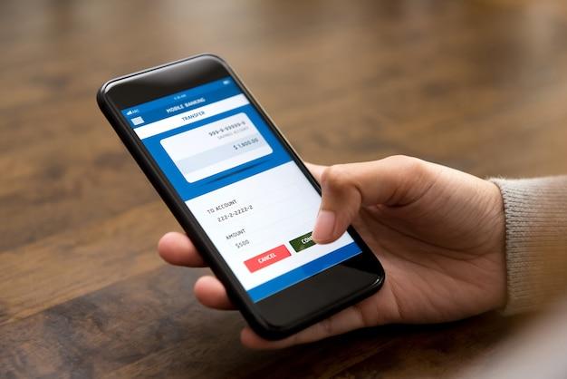 Il tocco della mano della donna conferma il pulsante sullo schermo dello smartphone, trasferendo i soldi online Foto Premium