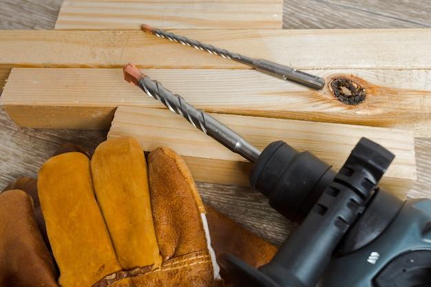 Il trapano a percussione elettrico si trova su un tavolo di legno Foto Premium