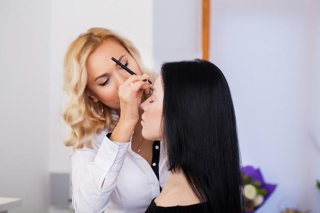 Il truccatore applica l'ombretto. volto di donna bella trucco perfetto Foto Premium