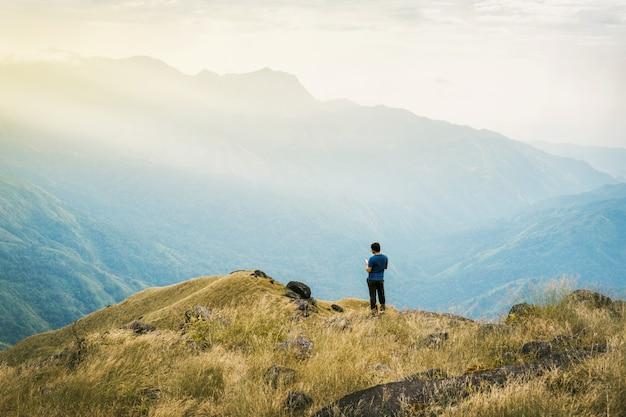 Il turista dell'asia del giovane del filtro da instagram alla montagna sta guardando sopra l'alba nebbiosa e nebbiosa di mattina Foto Premium