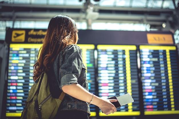 Il turista femminile di bellezza che esamina i programmi di volo per il controllo toglie il tempo Foto Premium