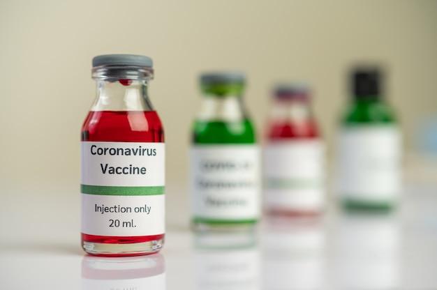 Il vaccino contro il covid-19 è in rosso e verde in bottiglie posizionate sul pavimento. Foto Gratuite