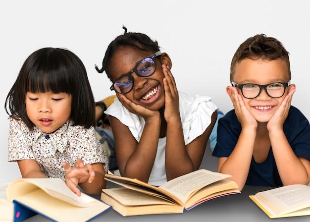 Il vario gruppo di bambini studia il libro colto Foto Premium
