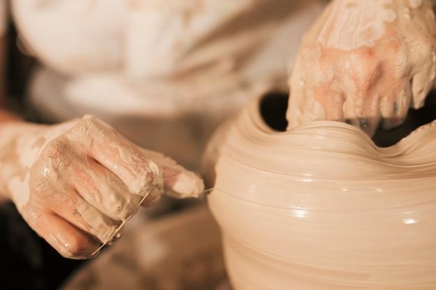 Il vasaio allinea la pentola di terracotta bagnata con il filo sulla ruota del vasaio Foto Gratuite
