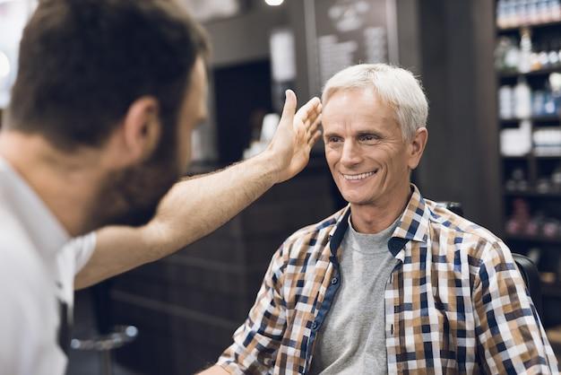 Il vecchio è seduto sulla sedia del barbiere. Foto Premium