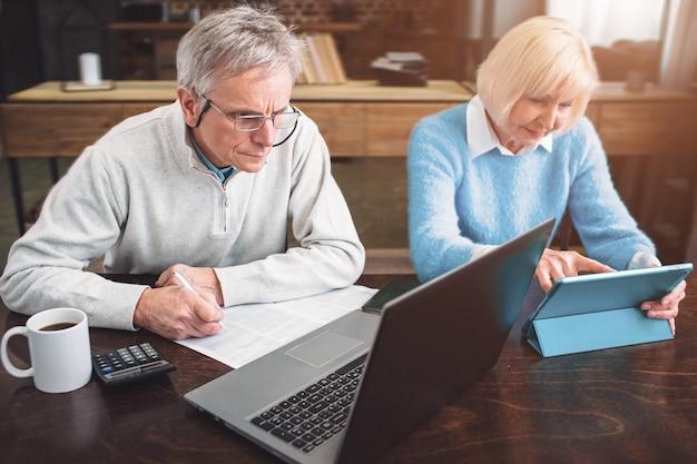 Il vecchio imprenditore e il suo partner stanno lavorando insieme su diversi laptop Foto Premium