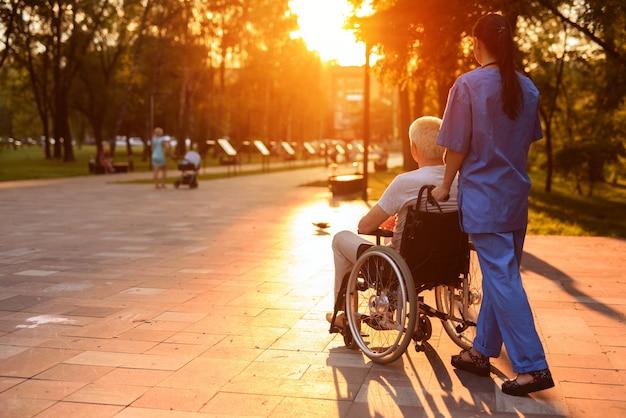 Il vecchio in sedia a rotelle e un'infermiera stanno camminando nel parco Foto Premium