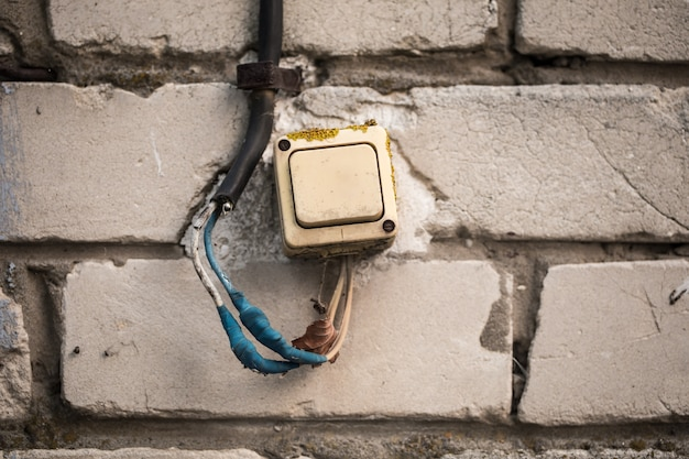 Il vecchio interruttore sul muro di mattoni, attorcigliava il nastro blu. Foto Gratuite
