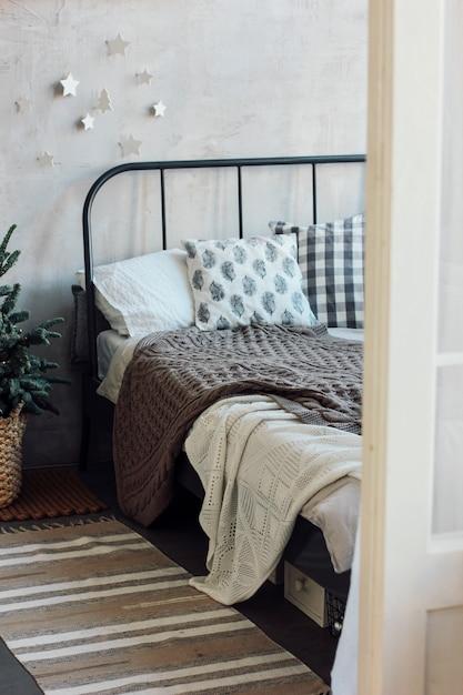 Il vecchio letto con cuscini e coperta a maglia. design natalizio minimalista Foto Premium
