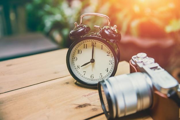 Il vecchio orologio con la retro macchina fotografica tiene il concetto di memoria e di tempo Foto Premium