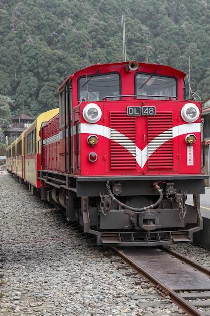 Il vecchio treno rosso in alishan line ritorna alla stazione ferroviaria di chiyi in una giornata nebbiosa. Foto Premium