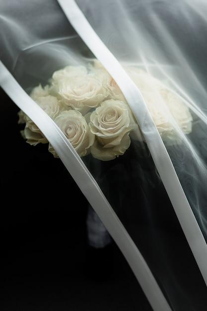 Il velo da sposa copre il bouquet di rose nuziali Foto Gratuite