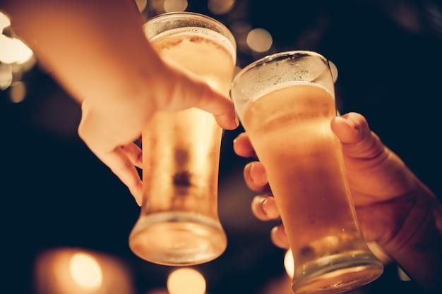 Il vetro della birra fredda si allaccia con bokeh bello, gli amici bevono insieme la birra, il tono scuro Foto Premium