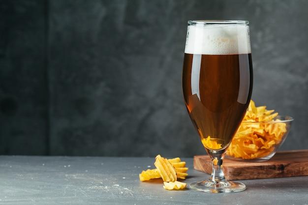 Il vetro di birra scura con la ciotola di spuntini della birra si chiude su Foto Premium