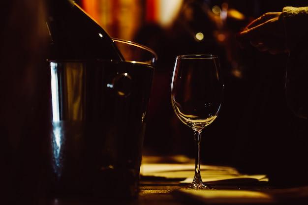 Il vetro illuminato è sul tavolo accanto alle bottiglie di vino in un secchio per il raffreddamento. chiave di basso Foto Premium