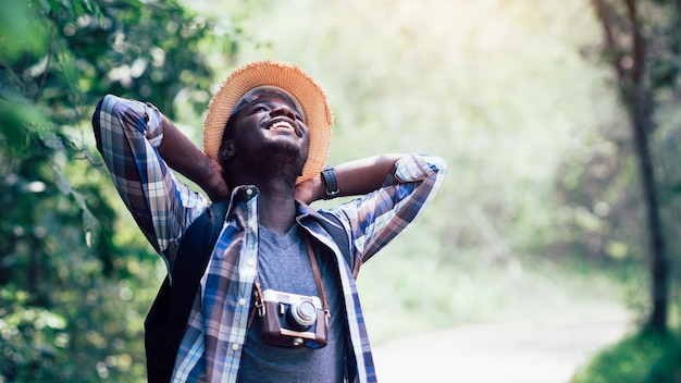 Il viaggiatore africano dell'uomo sorride e si rilassa nella giungla Foto Premium