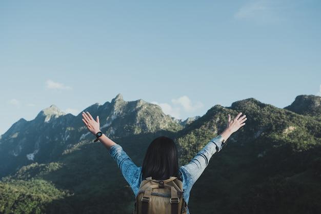 Il viaggiatore asiatico della donna arma su nell'aria alla vista della montagna Foto Premium