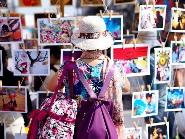 Il viaggiatore con zaino e sacco a pelo asiatico delle donne sta guardando le foto delle attrazioni turistiche nel festival del turismo della tailandia. Foto Premium