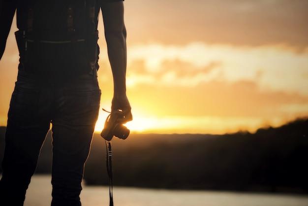 Il viaggiatore con zaino e sacco a pelo si rilassa sulla montagna con la macchina fotografica e il tramonto Foto Gratuite