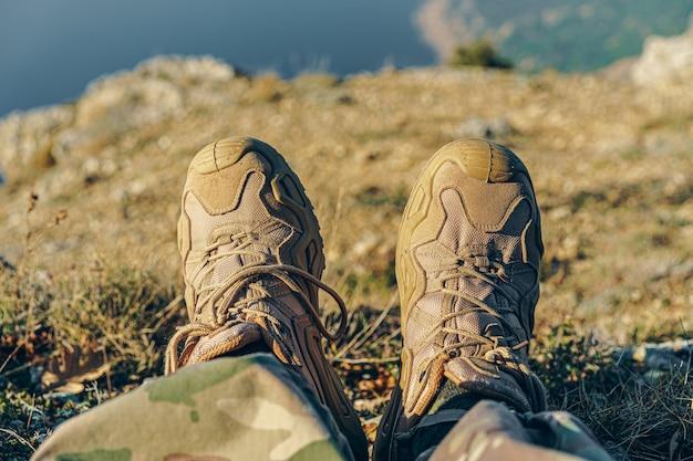 Il viaggiatore dell'uomo in stivali da trekking si siede sulla cima Foto Premium