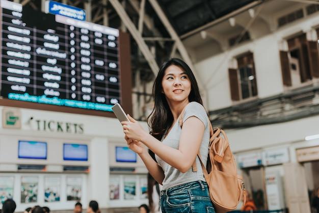 Il viaggiatore della donna usa la parte anteriore dello smartphone della cabina del biglietto Foto Premium