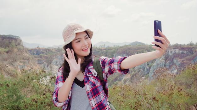 Il video asiatico del vlog della donna di viaggiatore con zaino e sacco a pelo di blogger sopra la montagna, giovane femmina felice facendo uso del telefono cellulare fa il video del vlog gode delle feste sull'escursione dell'avventura. Foto Gratuite